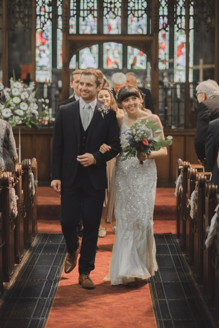 A happy couple walks down the aisle at St Peter's
